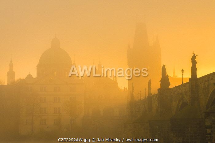 Charles Bridge with mist at sunrise, Prague, Bohemia, Czech Republic