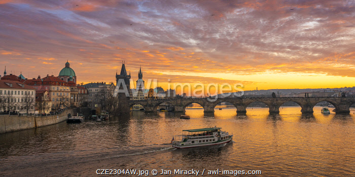 Boat going towards Charles Bridge and Church of Saint Francis of Assisi with Old Town Bridge Tower at sunset, Prague, Bohemia, Czech Republic