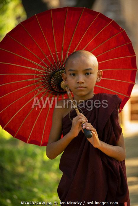 Portrait of novice monk with red umbrella, Bagan, Mandalay Region, Myanmar