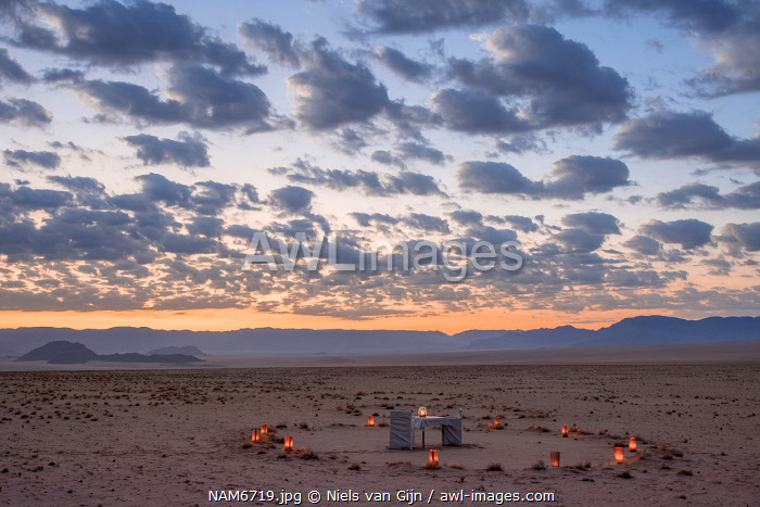 awl-images.com - Namibia / Namibia, NamibRand Nature Reserve, Kwessi Dunes, a dining table for two in the desert at sunset.