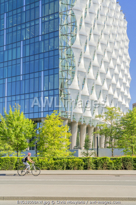 Cyclist riding past The American embassy in London, Nine Elms, London,England, UK