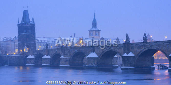 awl-images.com - Czech Republic / Charles Bridge and Old Town Bridge Tower against snowy sky in winter, Prague, Bohemia, Czech Republic