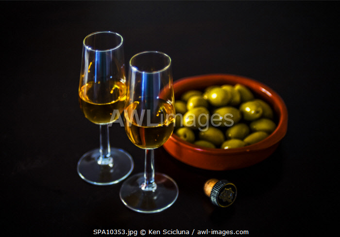 awl-images.com - Spain / Spain. Andalusia. Seville. Sherry a the traditional and prized Andalusian fortified wine in Spanish known as Jerez. It comes in various forms most notably as Manzanilla or Fino and Amontillado and Oloroso or the rarer Palo Cortado from various producers around the Jerez de la Frontera region in Andalusia. Here it is served with a tapas of green olives.
