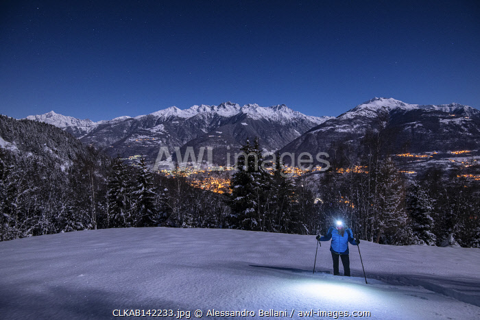 awl-images.com - Italy / Young girl with snowshoes in a night with full moon, Piazzola alp, Castello dell'Acqua, Sondrio Province, Valtellina, Lombardy, Italy, Europe (MR)