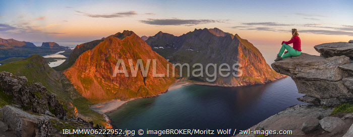 awl-images.com - Norway / Evening atmosphere, hiker on top of Ryten, sea, Kvalvika beach and mountains, Fredvang, Lofoten, Nordland, Norway, Europe